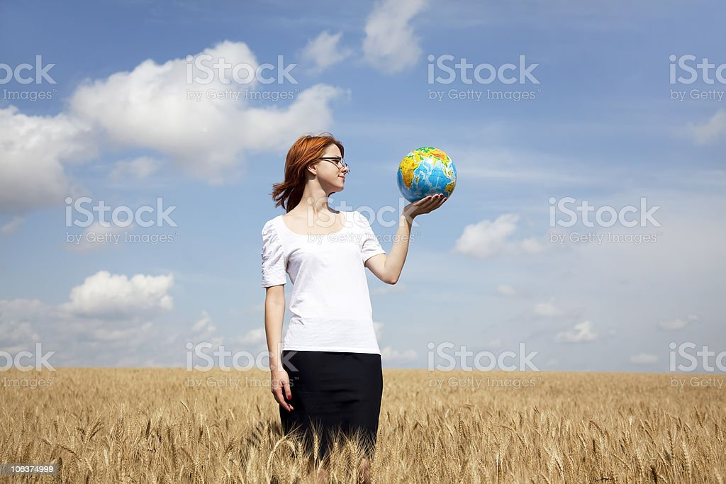 Young Businesswomen keeping globe in hand at wheat field stock photo