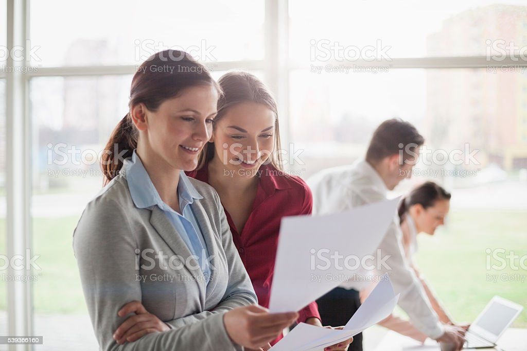 Young businesswomen reviewing documents with colleagues in background stock photo