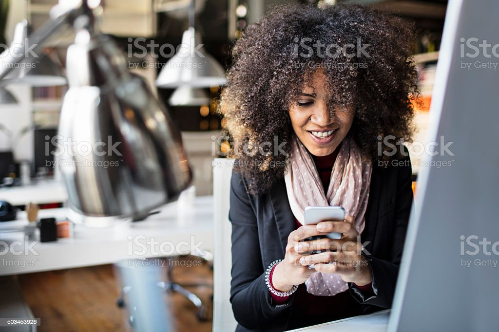 Young businesswomen texting on smartphone in the office stock photo