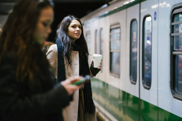 young businesswomen using public transport - milan railway foto e immagini stock