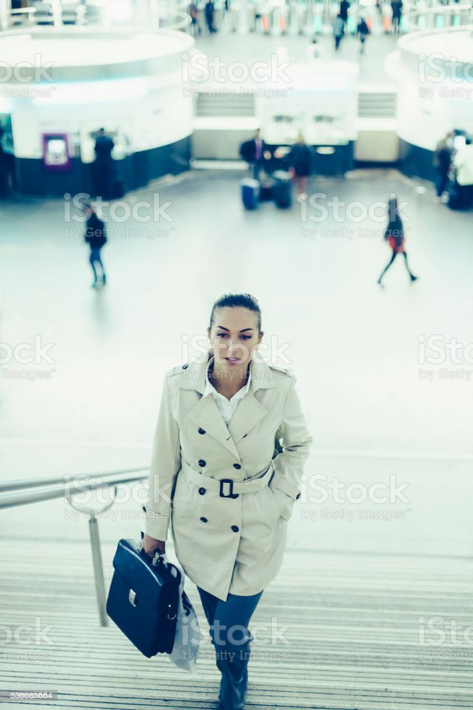 Young bussineswoman climbing up stairs in subway station stock photo