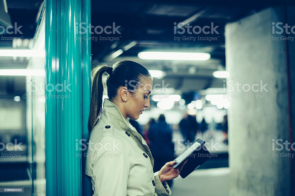 Young bussineswoman reading e-book on subway station stock photo