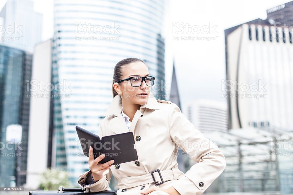 Young bussineswoman sitting and holding e-book on street stock photo
