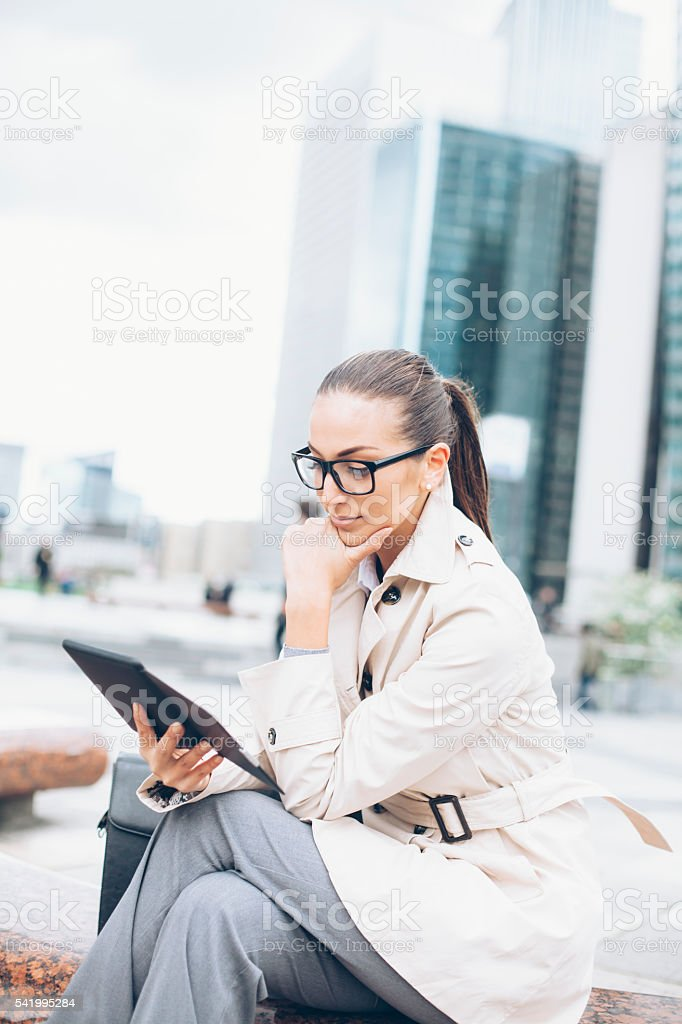 Young bussineswoman sitting and reading e-book stock photo