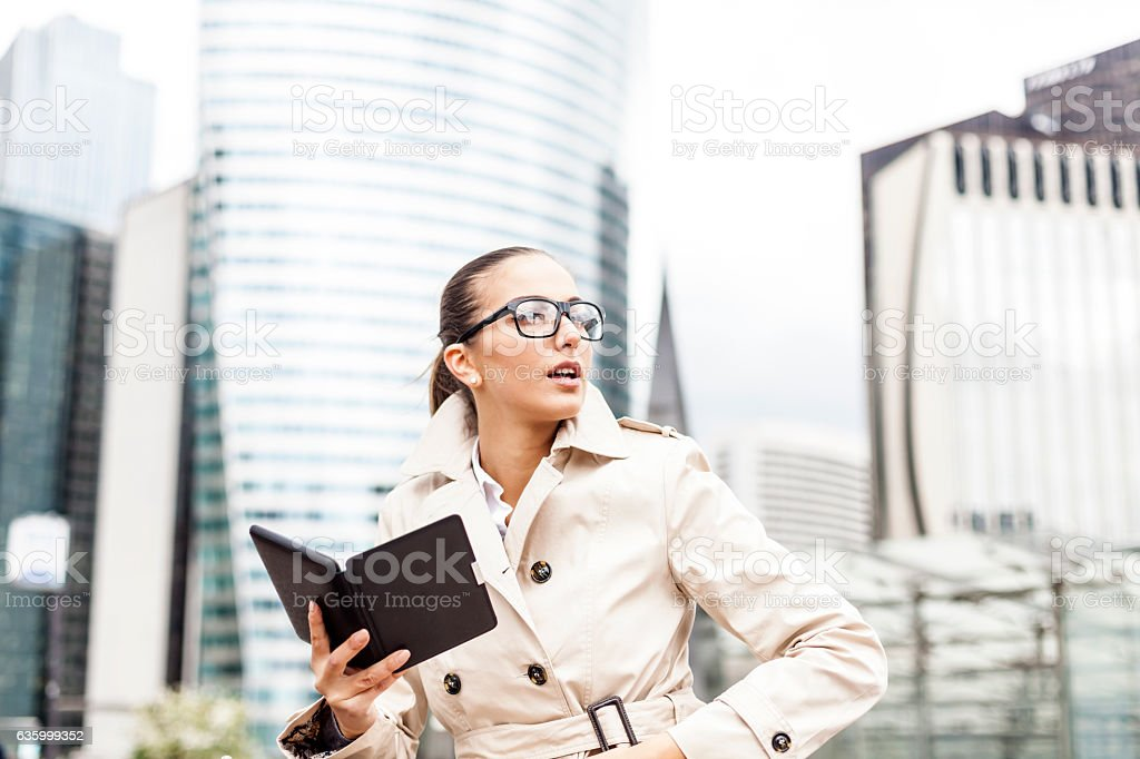 Young bussineswoman sitting and using e-book on street stock photo