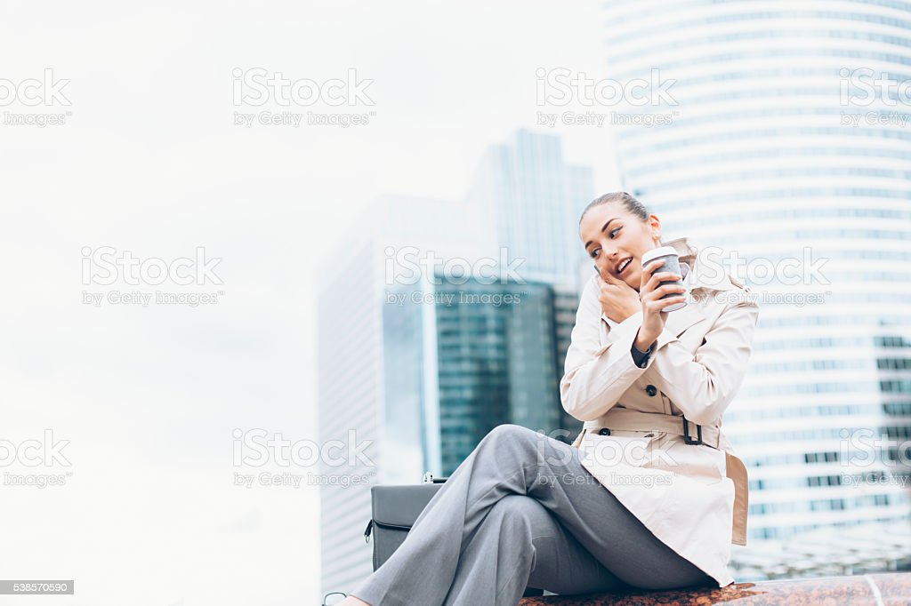 Young bussineswoman talking on the phone and drinking coffee stock photo