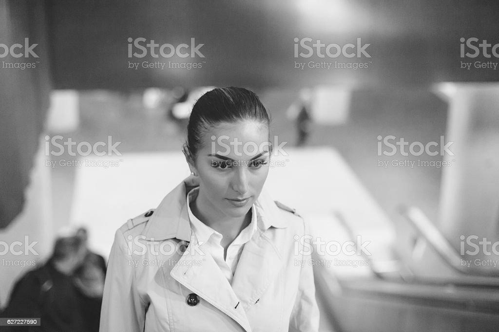 Young bussineswoman using escalator in subway station stock photo