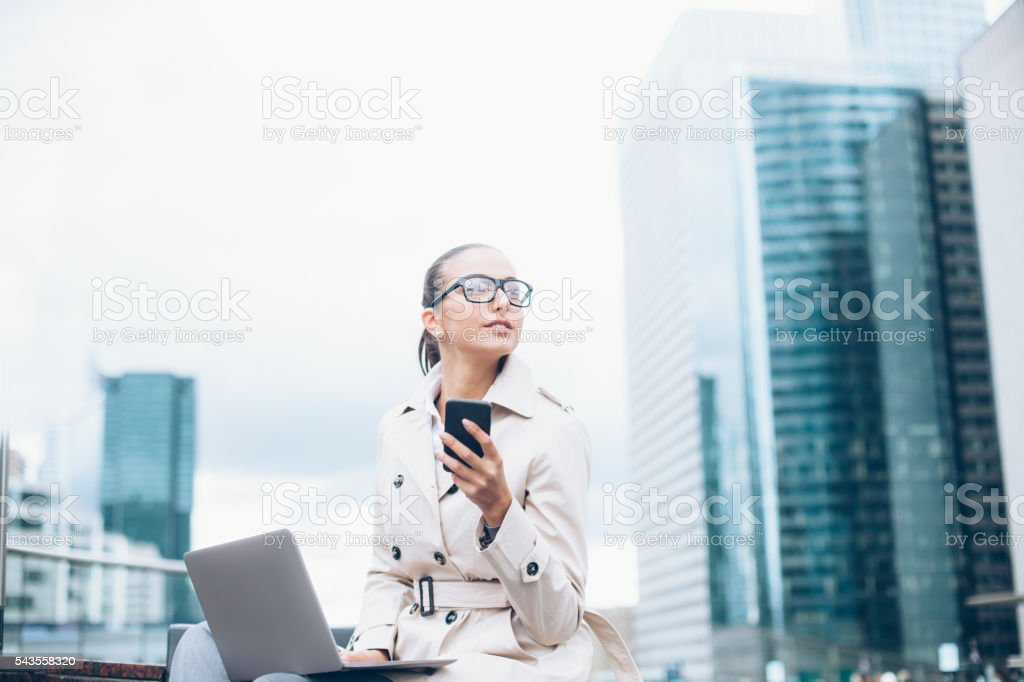 Young bussineswoman using laptop and phone on street stock photo