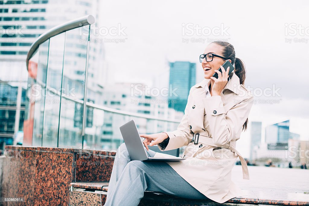 Young bussineswoman using laptop and talking on the phone stock photo
