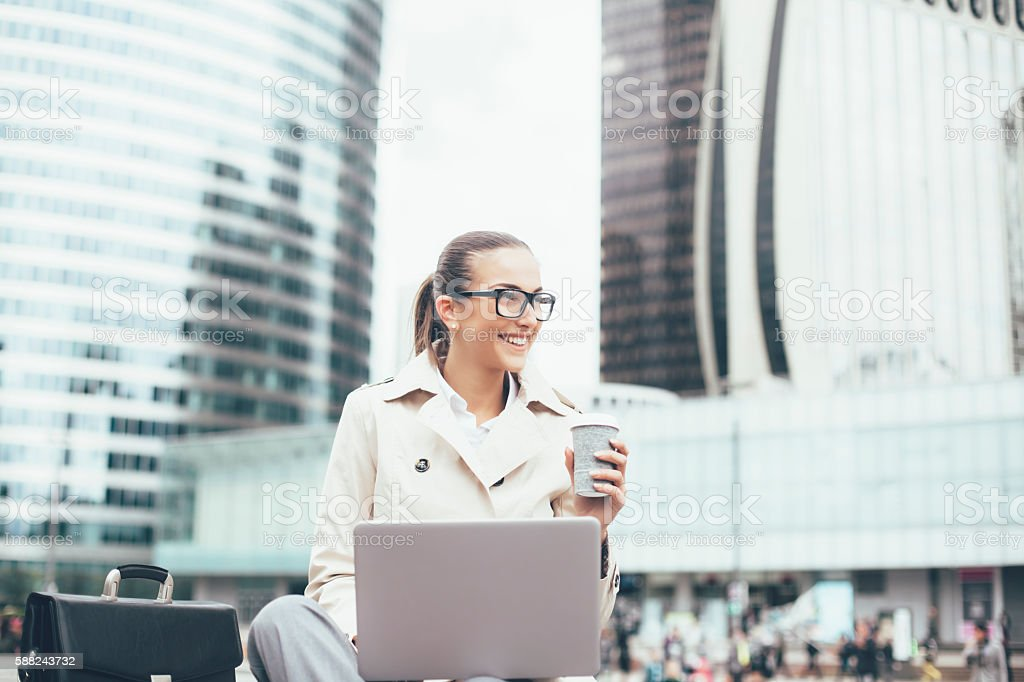 Young bussineswoman using laptop on street stock photo