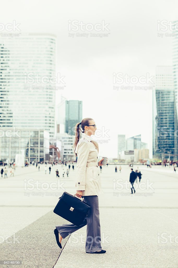 Young bussineswoman with bussines bag walking on street stock photo
