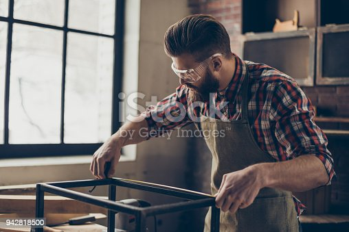 istock Young busy concentrated carpenter in checkered shirt with safety glasses holding a tape and measuring a metal frame at his workshop. 942818500