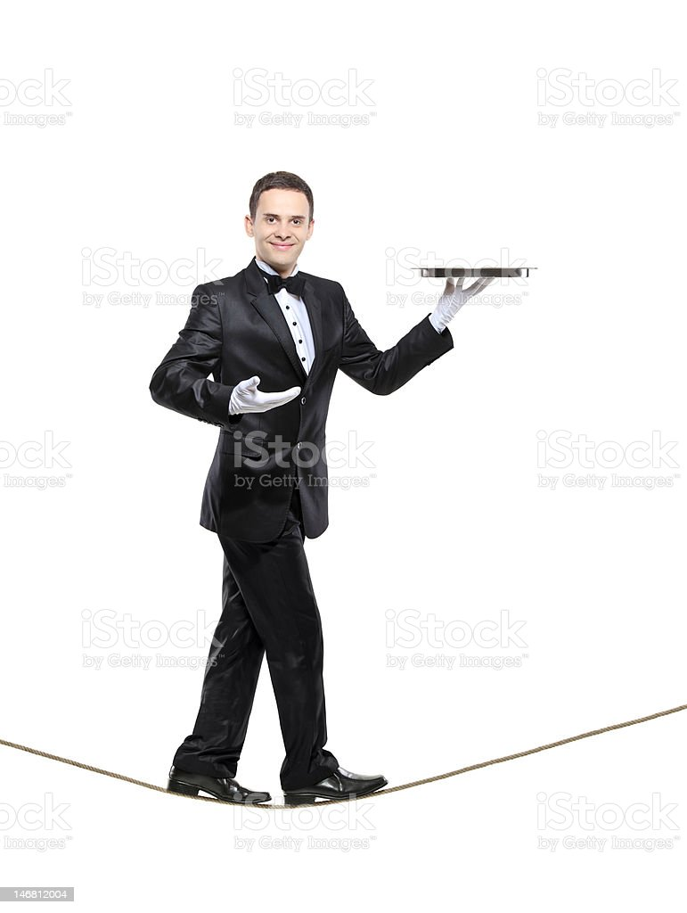 Young butler carrying a tray and walking on rope royalty-free stock photo