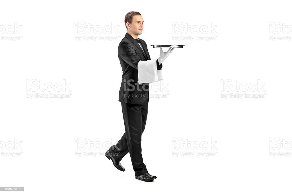 Young butler with bow tie carrying a tray stock photo
