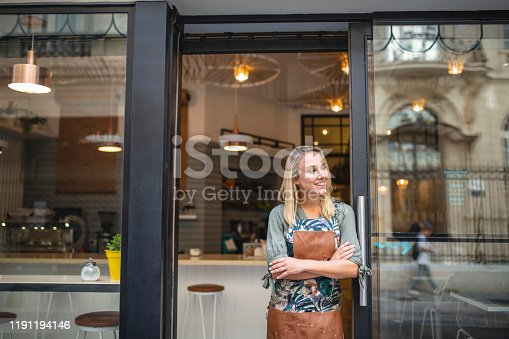 Hopeful Argentine female cafe owner standing in apron with arms crossed at open front door and looking away from camera.