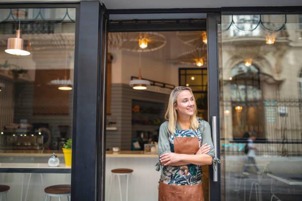 年輕的咖啡館老闆站在前門用武器交叉 - 商店 個照片及圖片檔