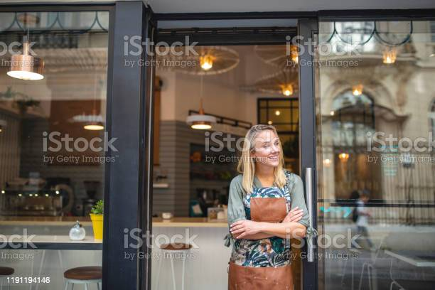 Young Cafe Owner Standing With Arms Crossed At Front Door - zdjęcia stockowe i więcej obrazów 25-29 lat