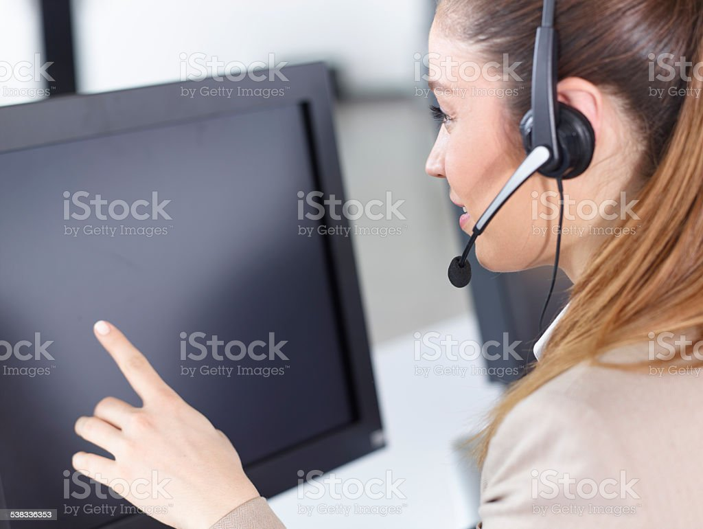 Young call centre representative talking phone and show something on...