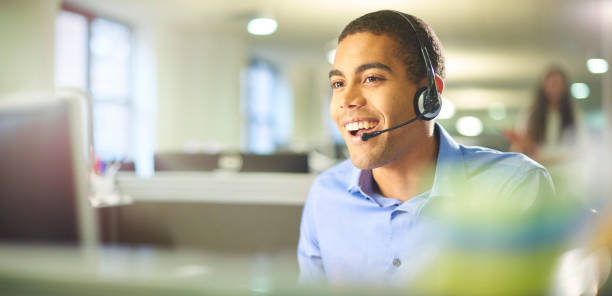 young call centre worker chatting. a young male call centre worker takes a call. hands free device stock pictures, royalty-free photos & images