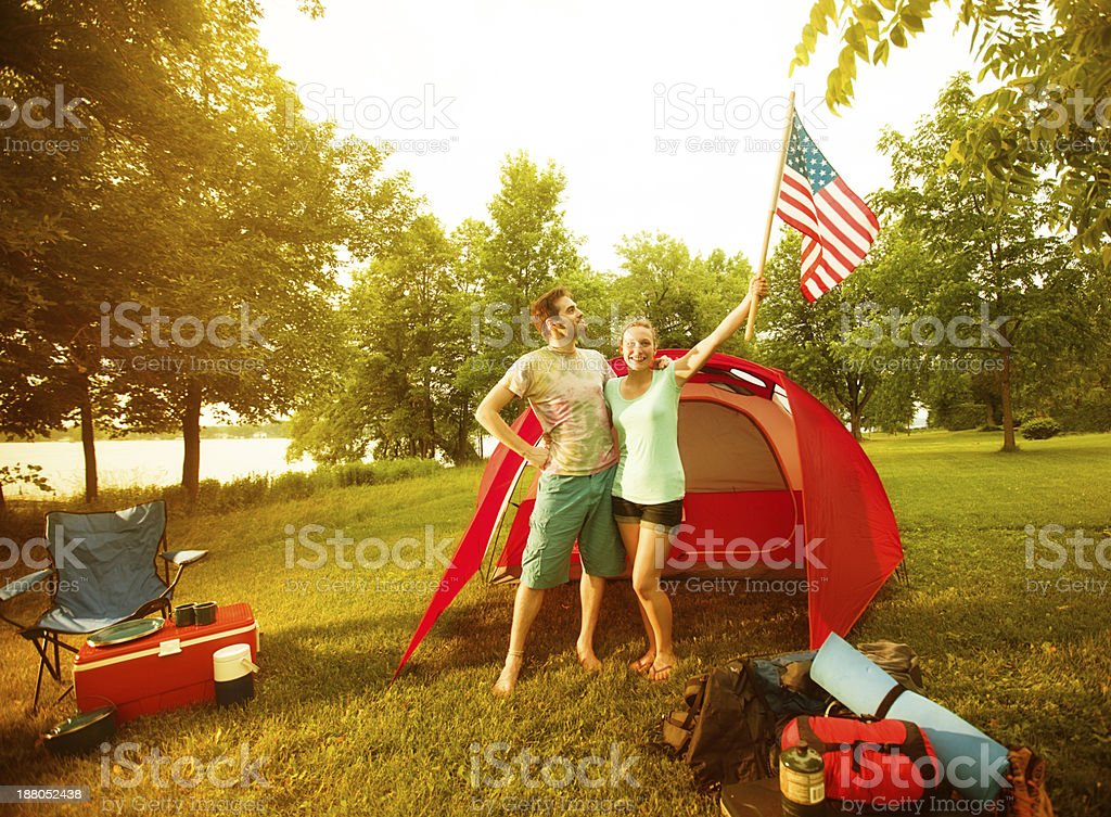 Young Camping Couple Waving U.S. Flag in Front of Tent stock photo