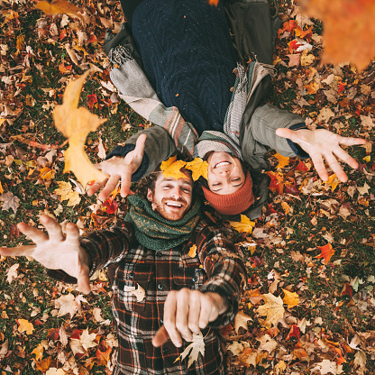 Cute young couple playing with autumn leaves.