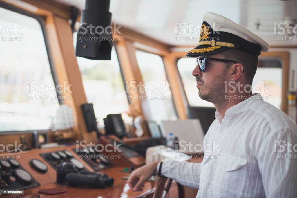 Young captain steering boat stock photo