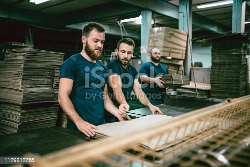 Young Carboard Factor Workers Trying A New Folding Technique