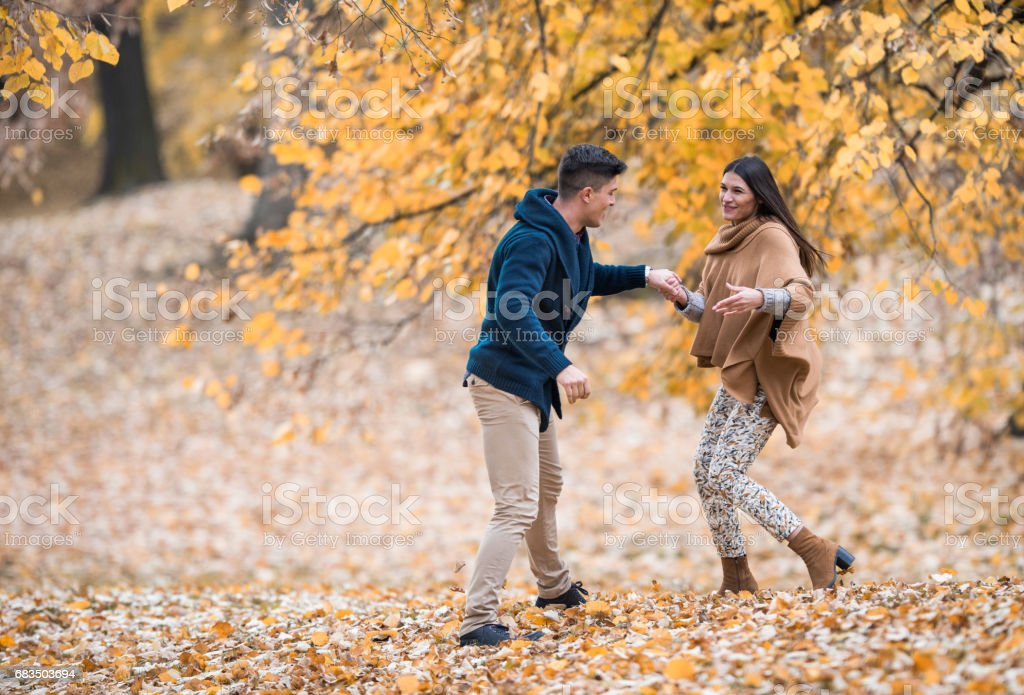Young carefree couple having fun during an autumn day in nature. stock photo