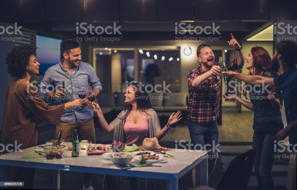Young carefree people having fun while toasting on a night party in front of their house. stock photo