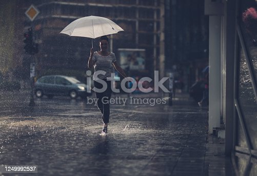 Full length of happy woman holding umbrella and running on the rain.