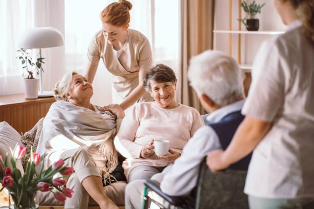 junge pflegerin tröstet ältere frau in pflegeheim - hospiz stock-fotos und bilder