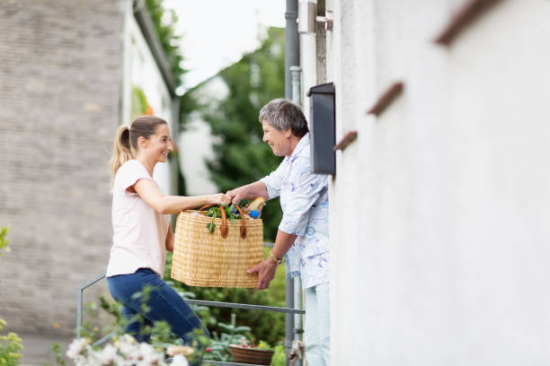young caregiver delivers groceries to senior woman stock photo