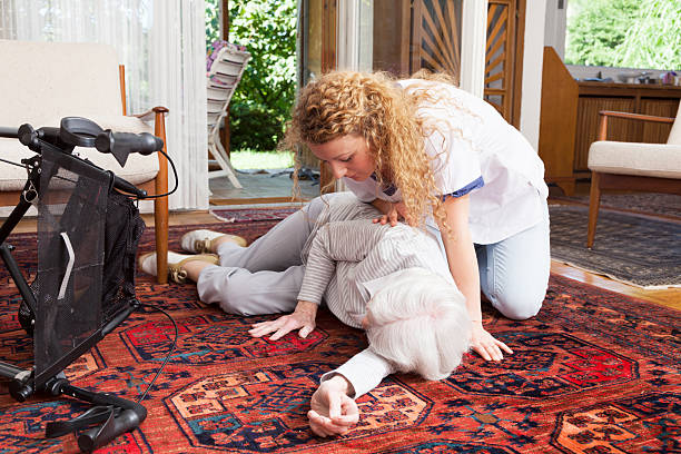 young caregiver looking after senior woman aftter accident stock photo
