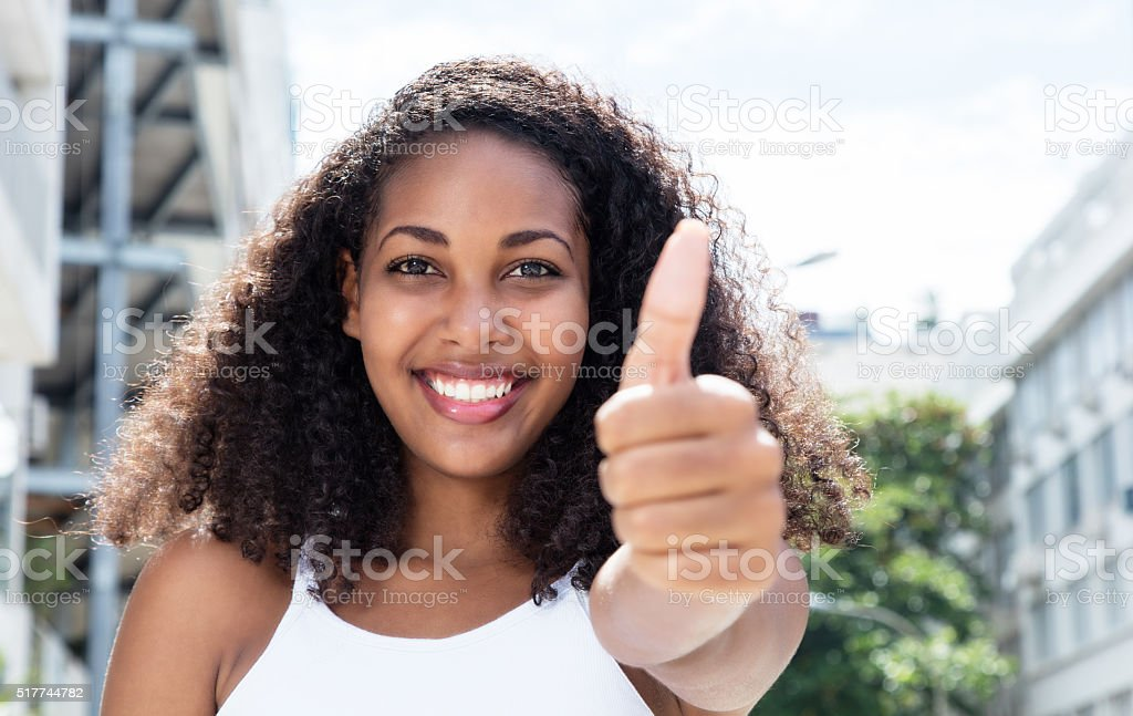 Young caribbean woman with curly hair in city showing thumb stock photo