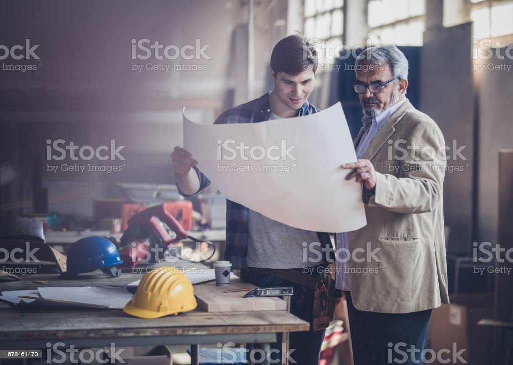 Young carpenter and his customer looking at blueprints in a workshop. royalty-free stock photo