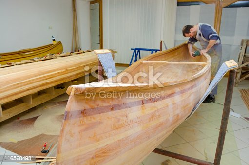 Young carpenter sandpapering wooden canoe of his own design.