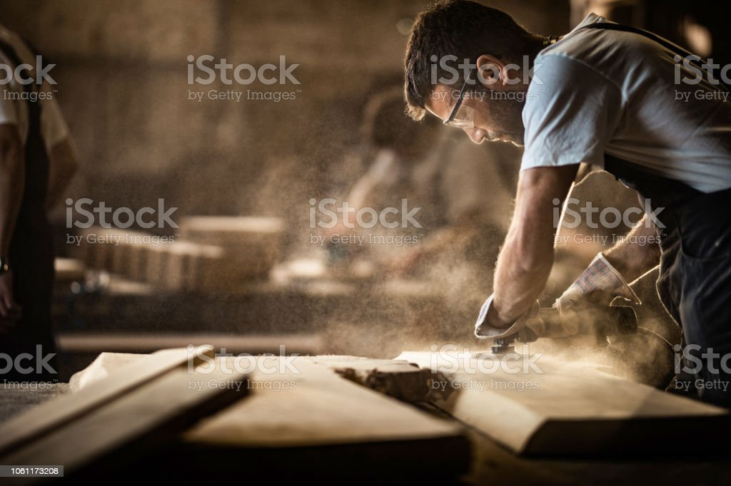 Young carpenter using sander while working on a piece of wood. stock photo