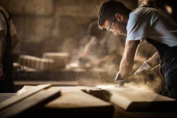 Young carpenter using sander while working on a piece of wood. Manual worker using sander while working on a wood in carpentry workshop. repairman stock pictures, royalty-free photos & images
