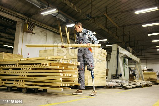 Young carpenter standing and carrying wood plank in wooden factory