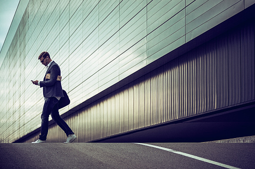 istock Young casual businessman using smartphone in the urban environment 492708472