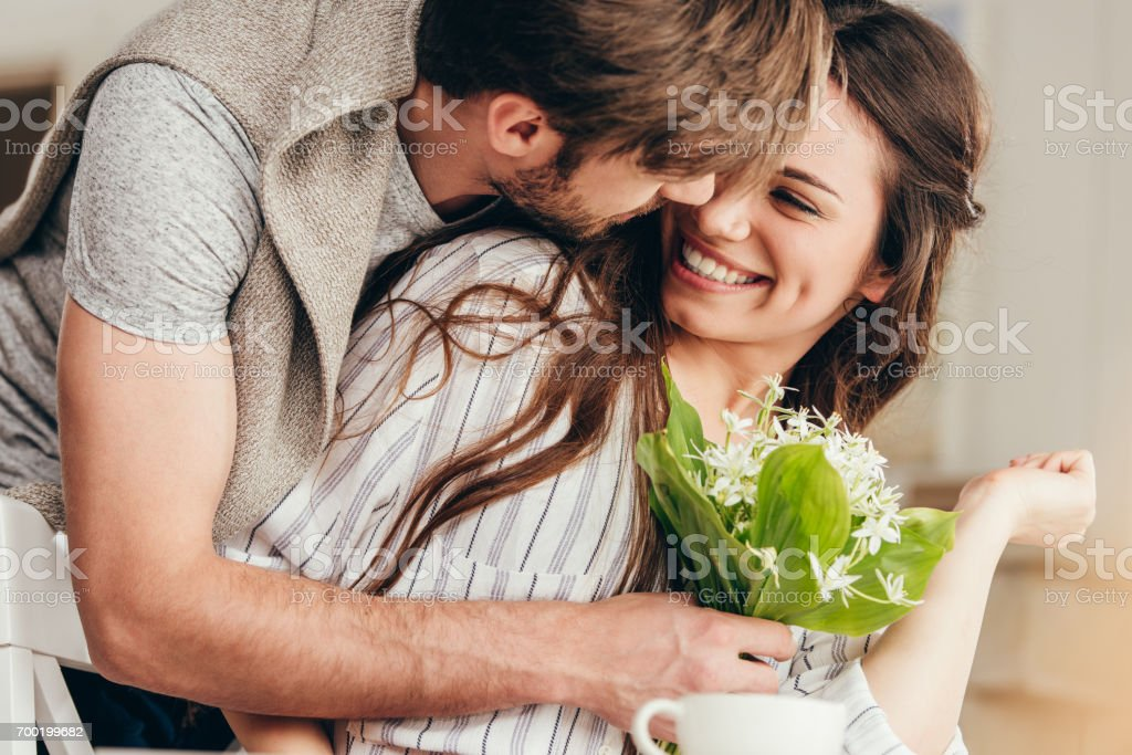 young casual couple embracing with bouquet of flowers at home stock photo