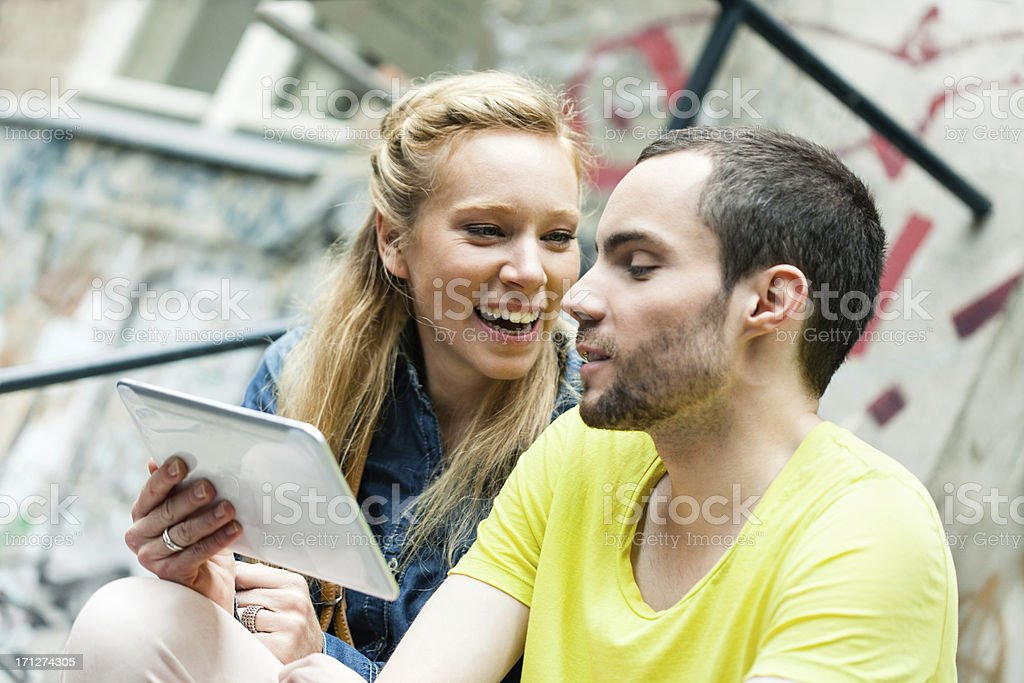 Young casual couple using digital tablet outdoors royalty-free stock photo