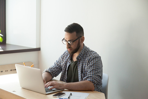 905545264 istock photo Young casual employee in glasses working on laptop in office 889206810