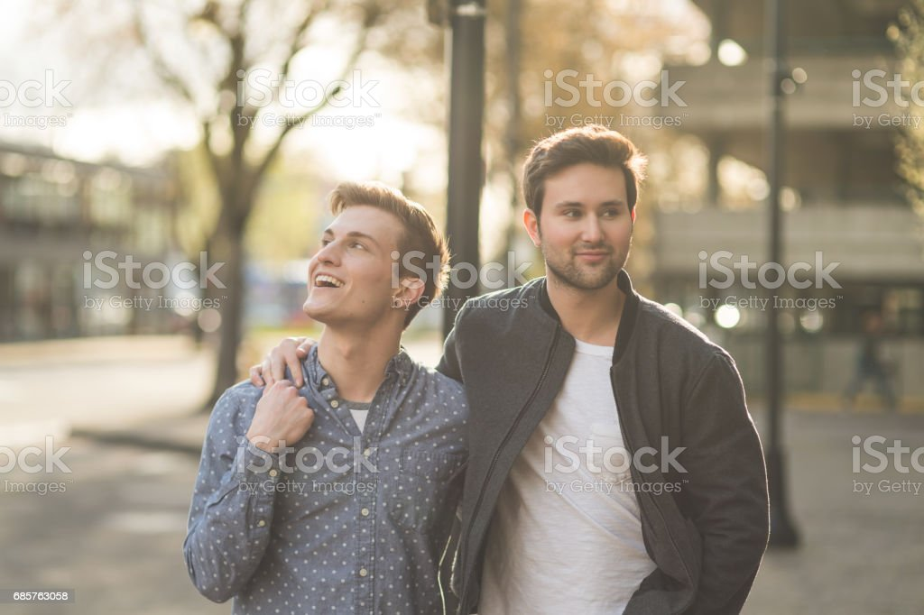 Young casual gay male couple walking in city foto stock royalty-free
