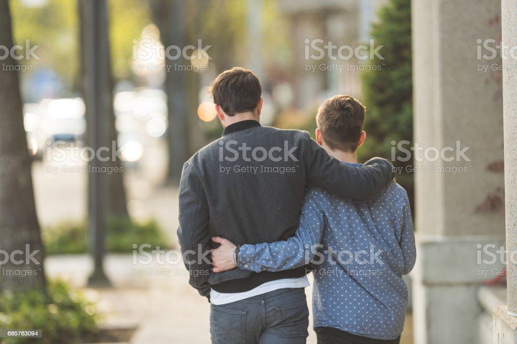 Jeune couple mâle gay occasionnel promenade dans la ville photo libre de droits