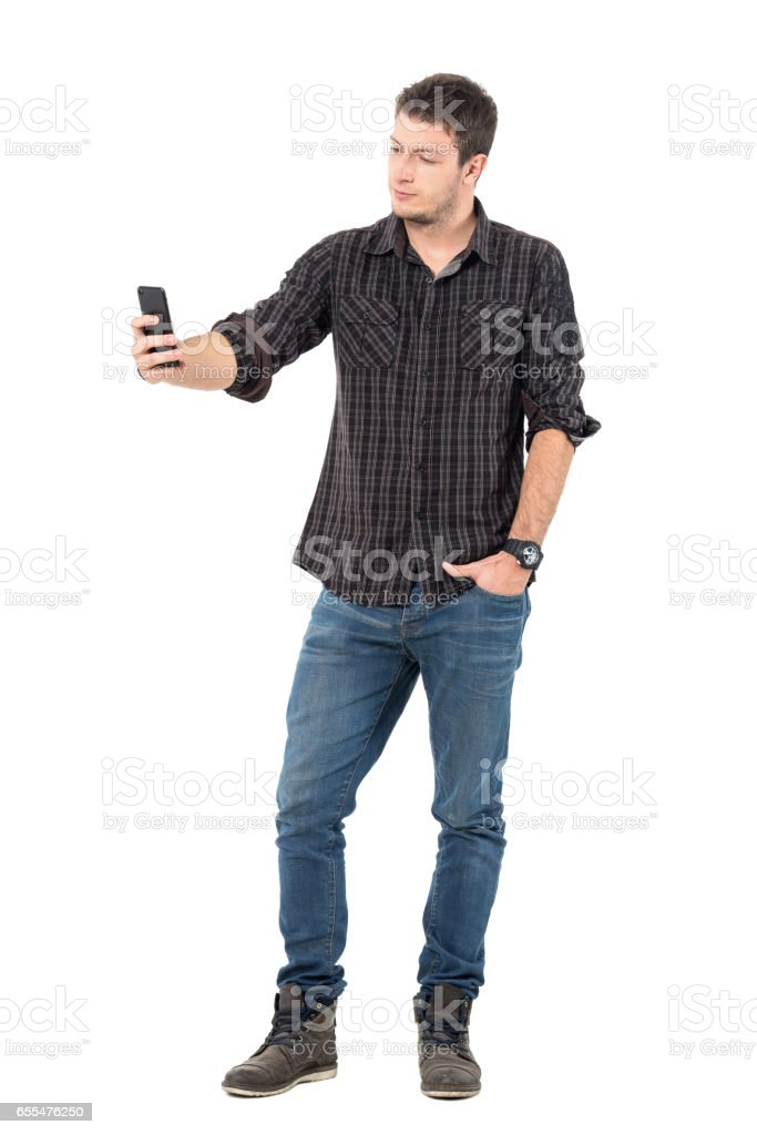 Young casual handsome man taking low angle selfie with smart phone stock photo