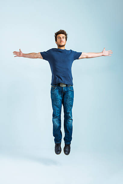 young casual man jumping - arms outstretched stock photos and pictures