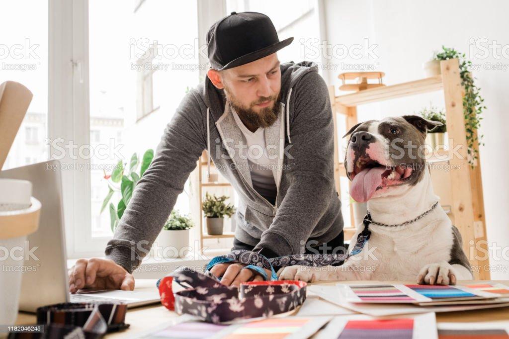 Junger Gelegenheitsmann, der seinen Hund anschaut, während er sich über den Arbeitsplatz beugt - Lizenzfrei Arbeiten Stock-Foto