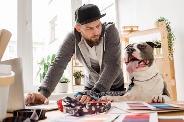 Junger Gelegenheitsmann, der seinen Hund anschaut, während er sich über den Arbeitsplatz beugt – Foto