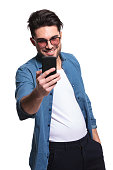 Happy young casual man smiling while texting from his smartphone. Isolated.